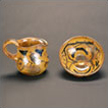 Yellow gold decorated pitcher in saucer